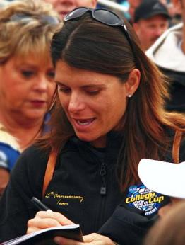 Image shows subject of article, Mia Hamm, signing an autograph.