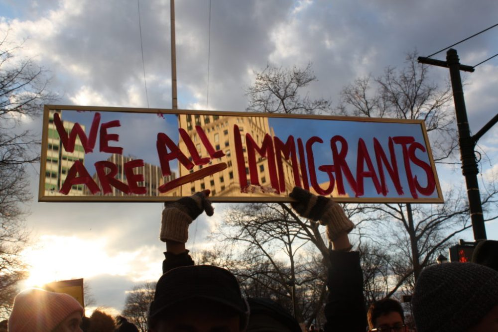 "Protesters hold up ""we are all immigrants"" sign at protest."