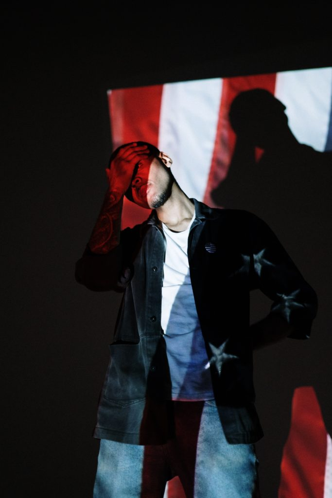 Man with an image of the American flag projected onto his body.