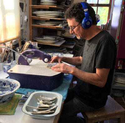 Paul Scott Cutting Transferware in is studio.