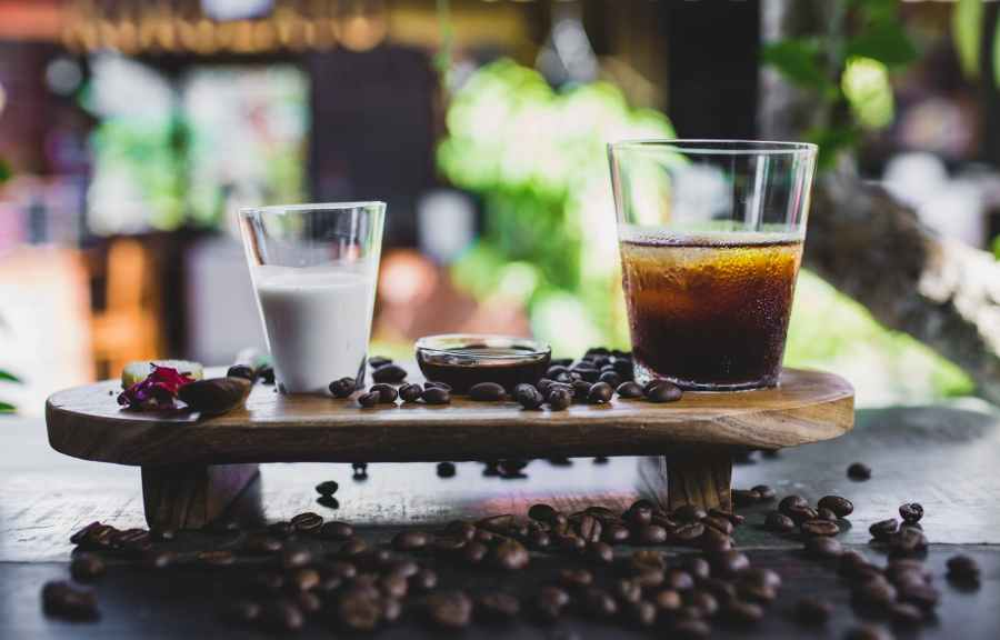 glass of cold coffee served with milk and beans