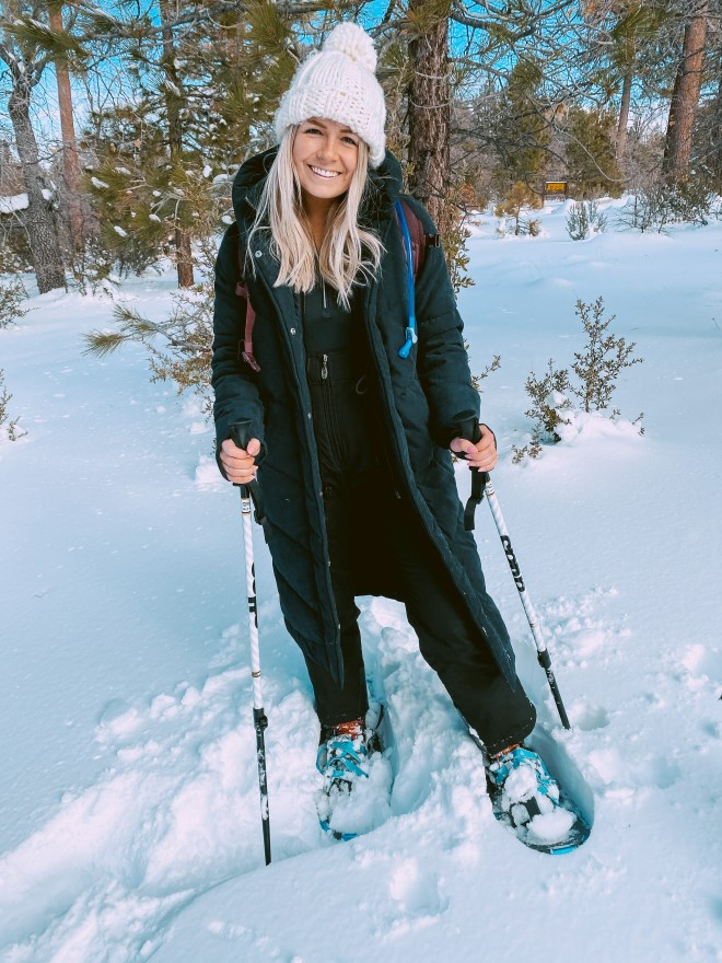 Ariana wearing the Ultra Long Puffer standing in the snow wearing snow shoes