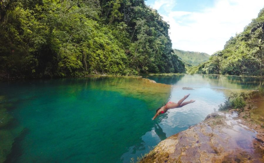 travel girl in guatemala dives in the natural emerald pools of semuc champey