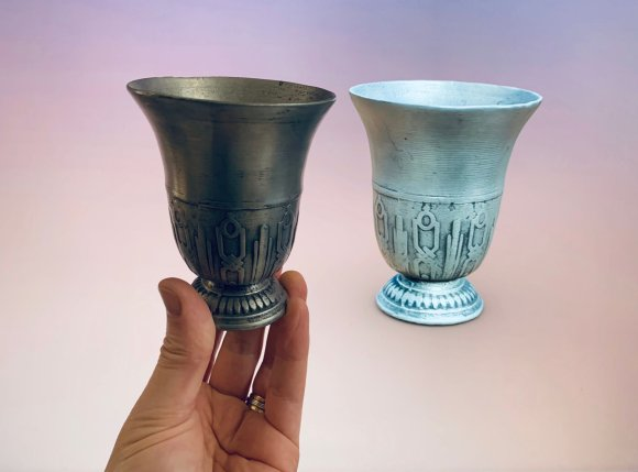 A pewter goblet is held up against a computer screen which is displaying a 3D replica of the same item, the whole image bringing the physical and virtual together.