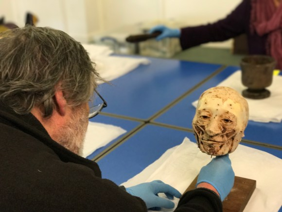 Main contemplates a wax model of a ancient human's head and face with little pin marks over it.