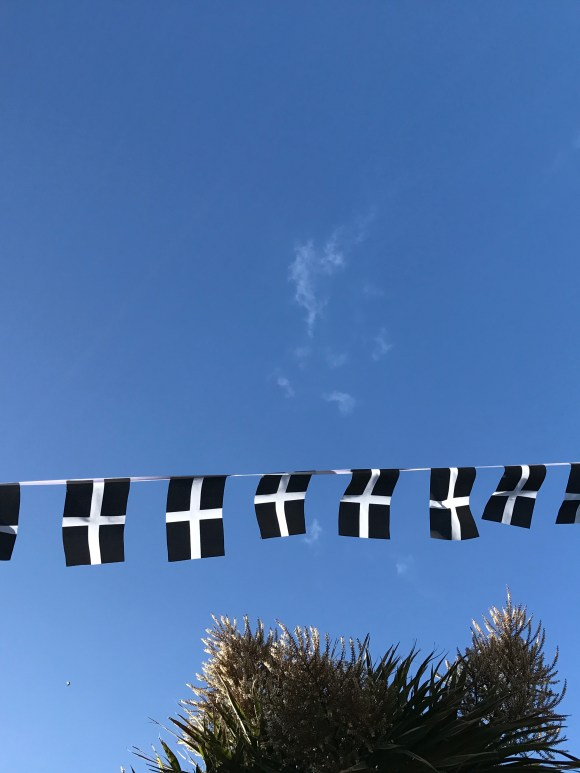 St Piran's Flag (black with white cross) bunting against a blue sky.