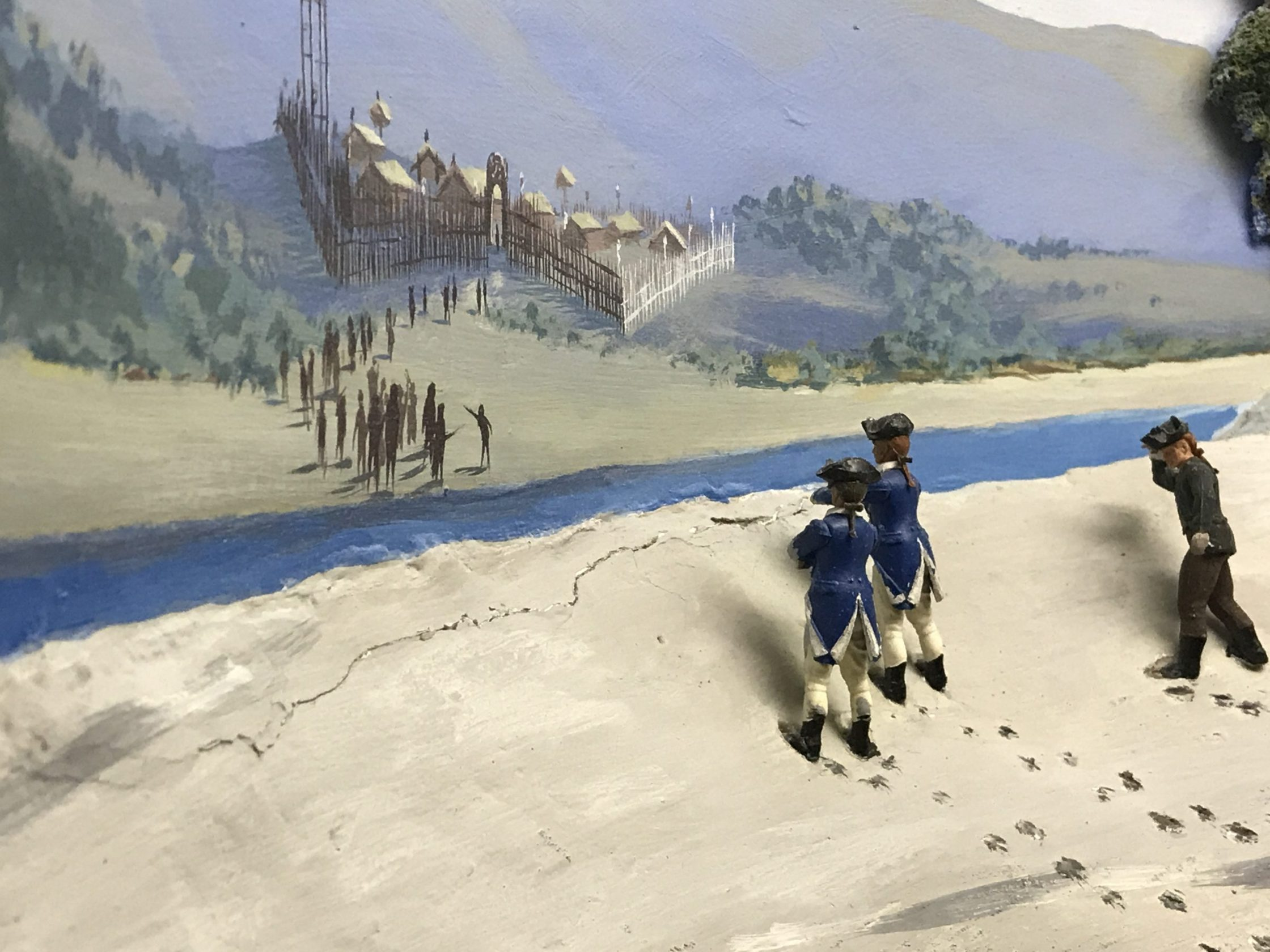 Diorama showing model soldiers wearing British navy uniforms from the late 18th century as the shores of eastern New Zealand. In the background flat brown painted figures with no features representing Māori.