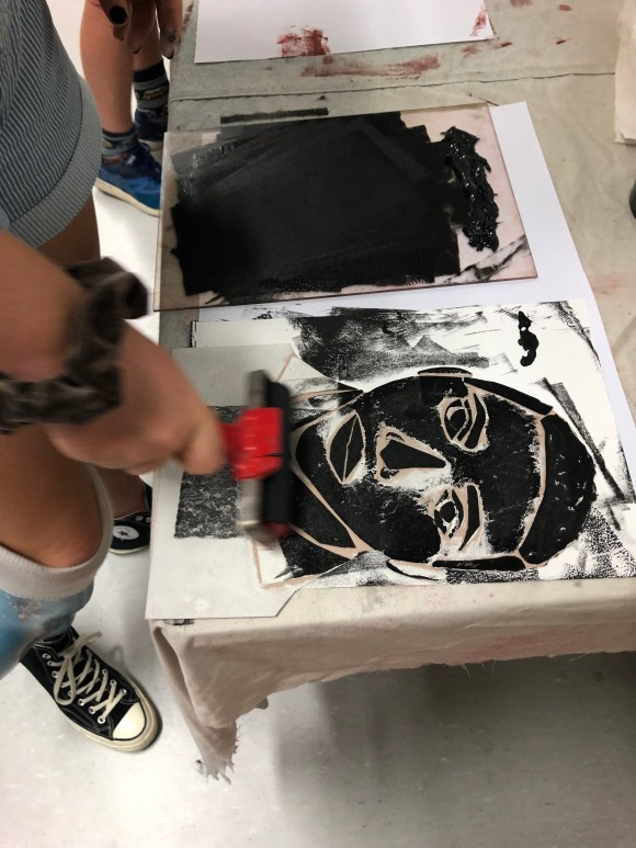 Printmaking in action, hand with stencil of face in relief bring painted