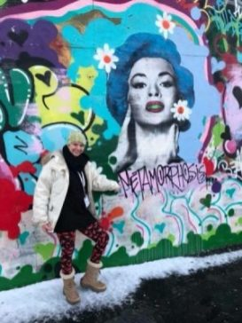 Brianna standing beside a mural in the snow