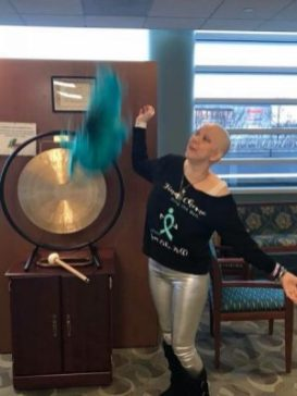 Brianna a young woman with low grade serous ovarian cancer ringing the bell to signify the finishing of her chemo treatment