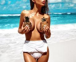 パイナップルで乳を隠す女性