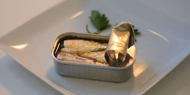 A can of sardines in oil on a white plate