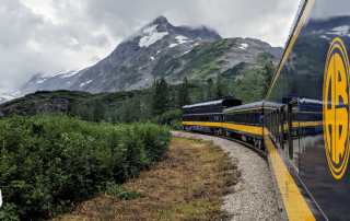Alaska Railroad train approaching a glacier and mountains on the Glacier Discovery Train