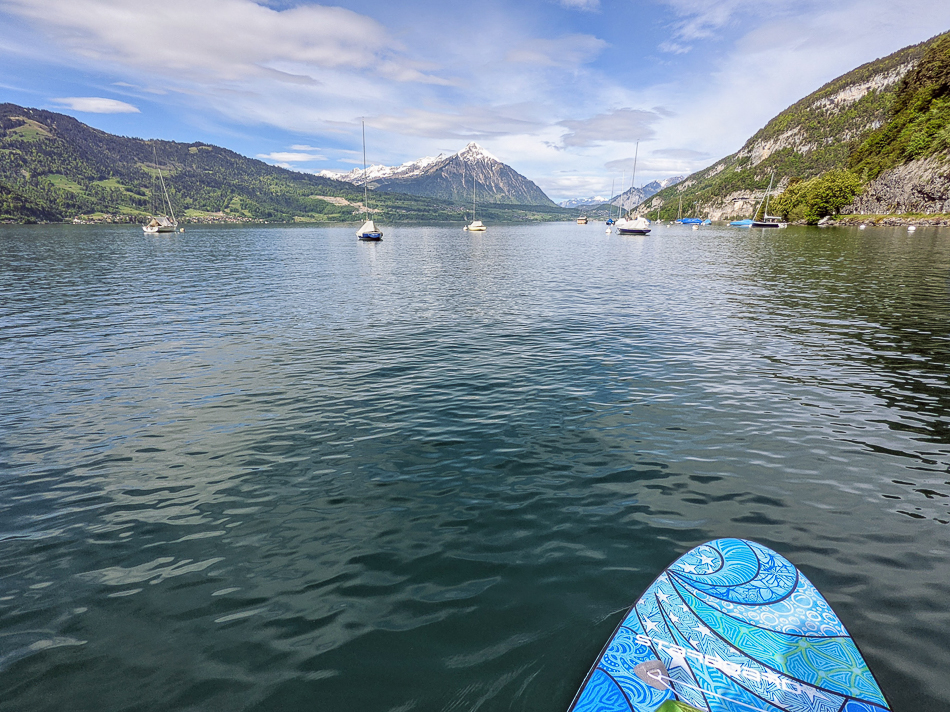 Paddleboard on a Swiss lake with mountains and sailboats