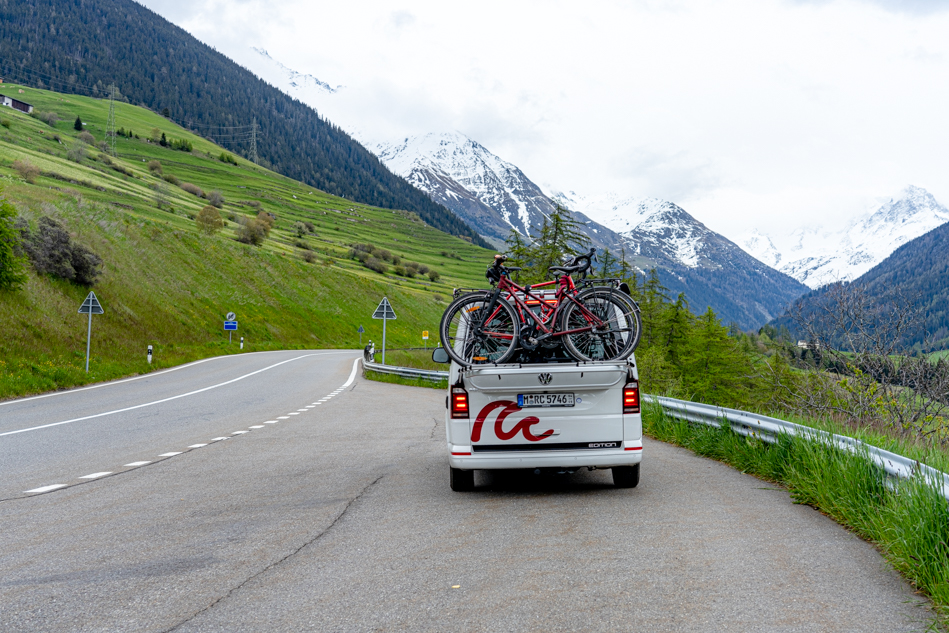 VW Campervan with two bikes on the back driving up a mountain road