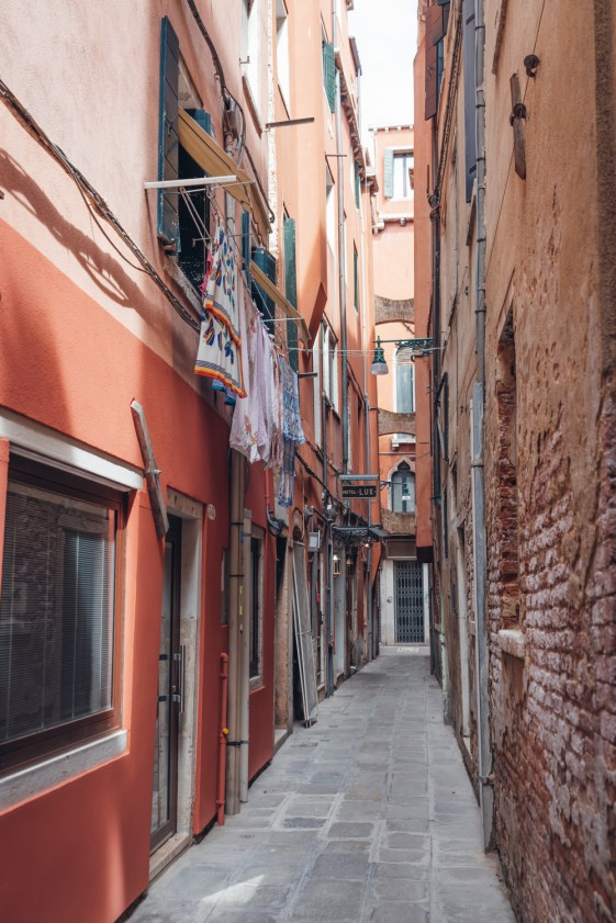 Venice alley with brick homes and laundry sustainable itinerary