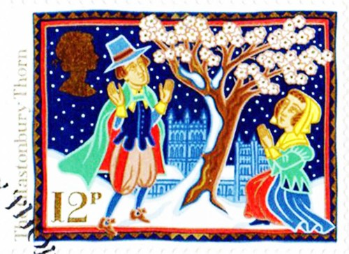 Postage stamp of man and woman in snow looking at the Holy Thorn blooming. Glastonbury Abbey is in the background.