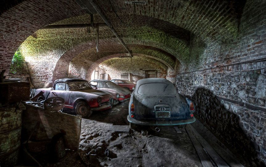 Abandoned dusty and dirty Alpha Romeo cars in a underground storage.