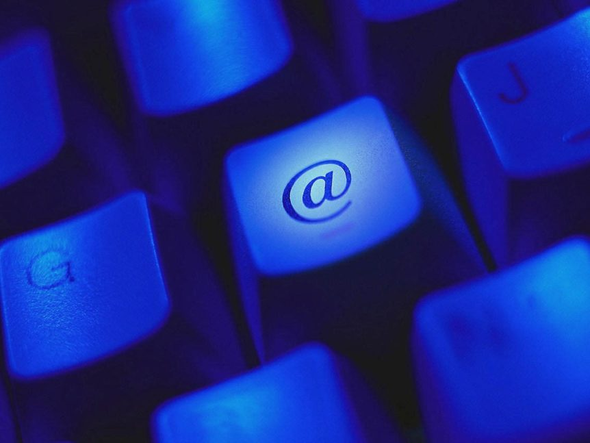 Keyboard in blue light with a key centered in frame with the @ (at sign).