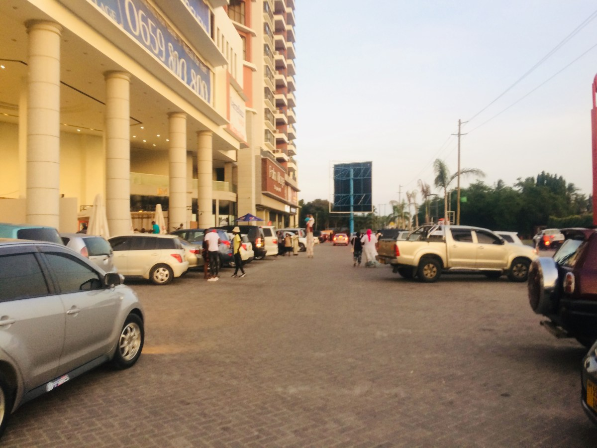People in parking lot of Palm Village Mall in Dar Es Salaam, Tanzania