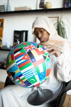black woman searching country on globe