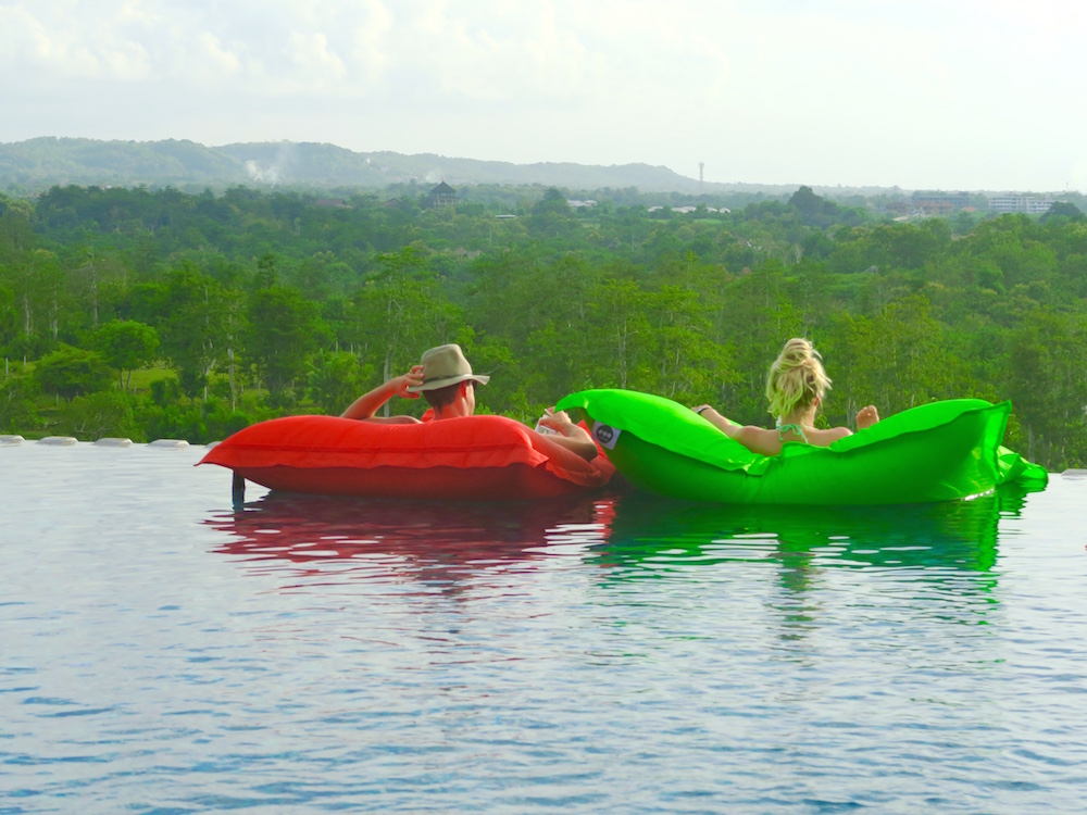 Couple floating on FatBoys in pool bar Unique Bali |curlytraveller.com
