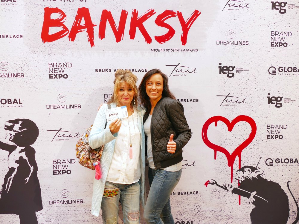 Woman with stepdaughter at Banksy exhibit in Amsterdam   curlytraveller.com