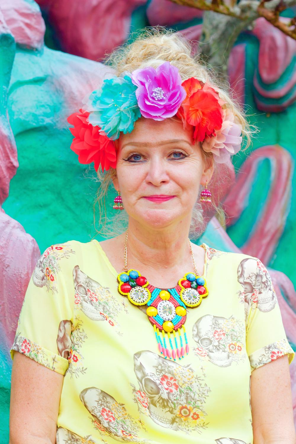Woman with flowers in her hair and yellow top in Haw Par Villa |curlytraveller.com