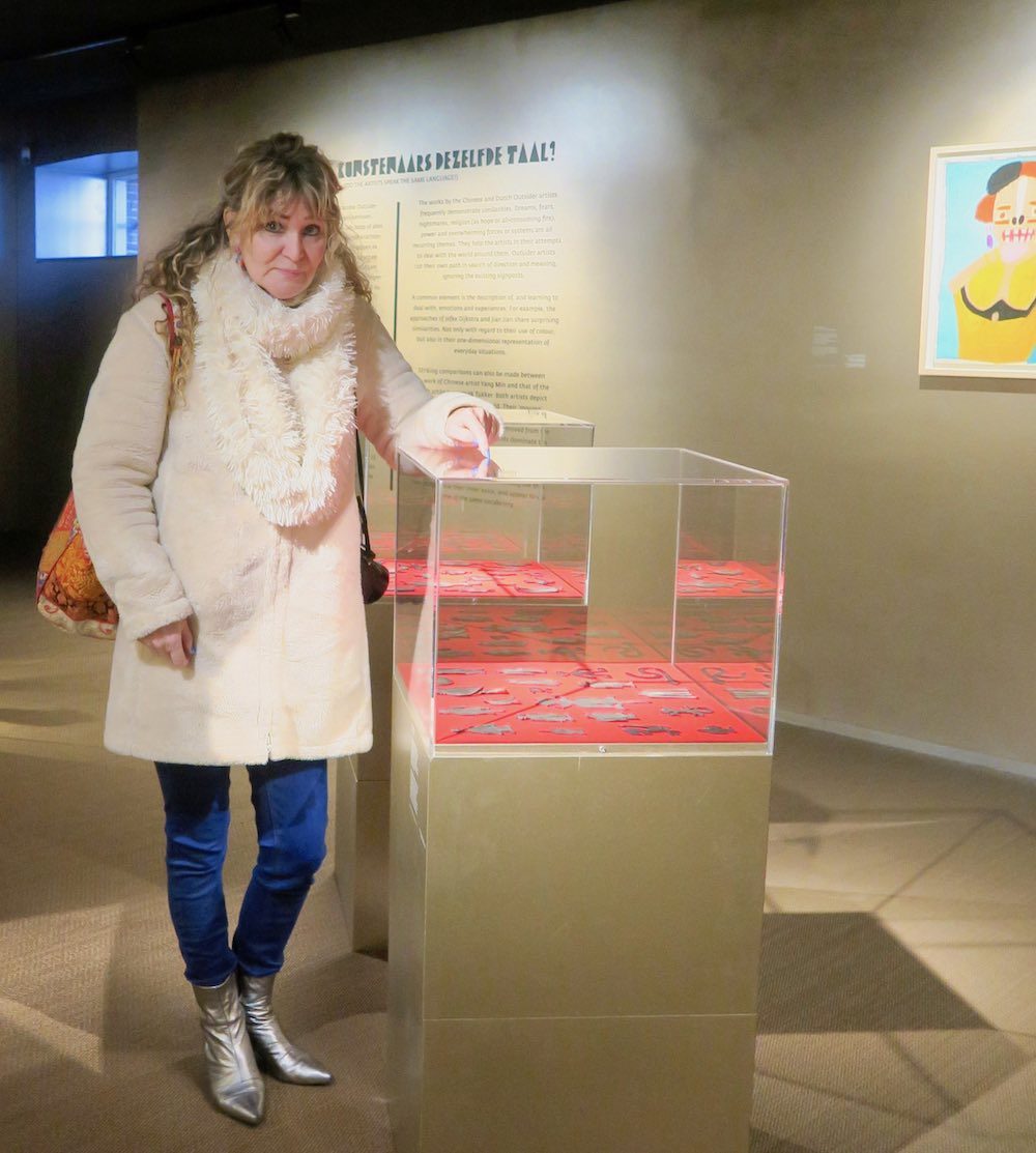 Woman pointing at art in display in Outsider Art Museum Amsterdam |curlytraveller.com