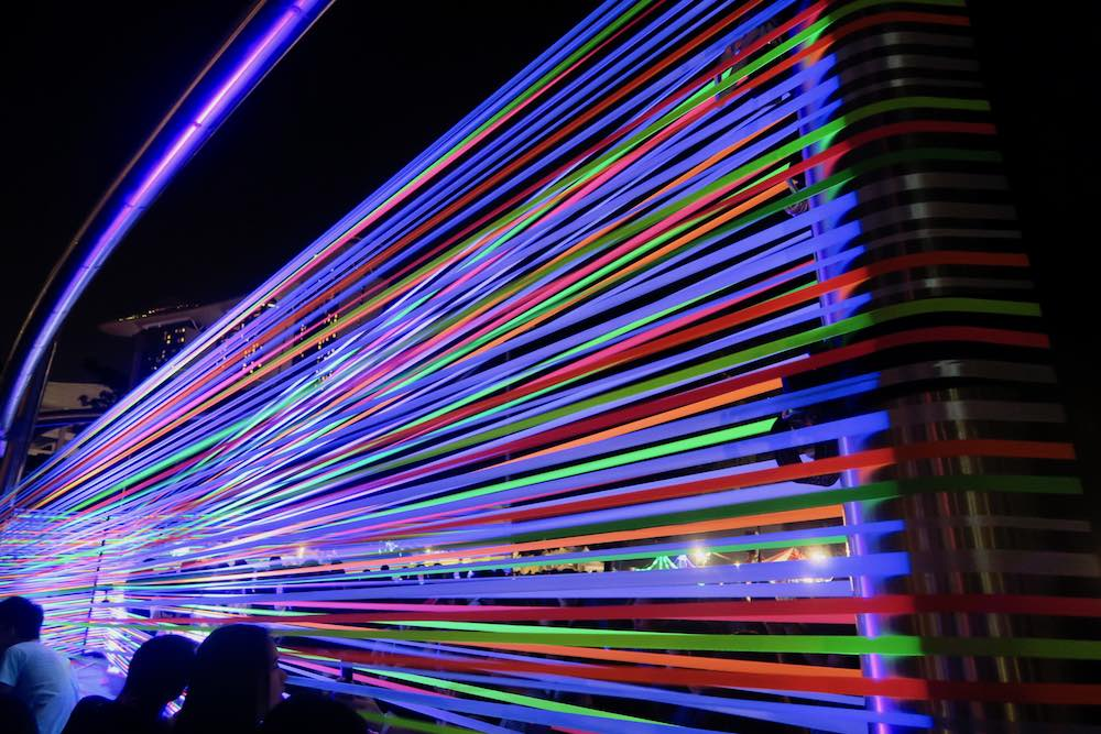 People taking selfies in front of coloured ribbons at iLight Marina Bay |curlytraveller.com