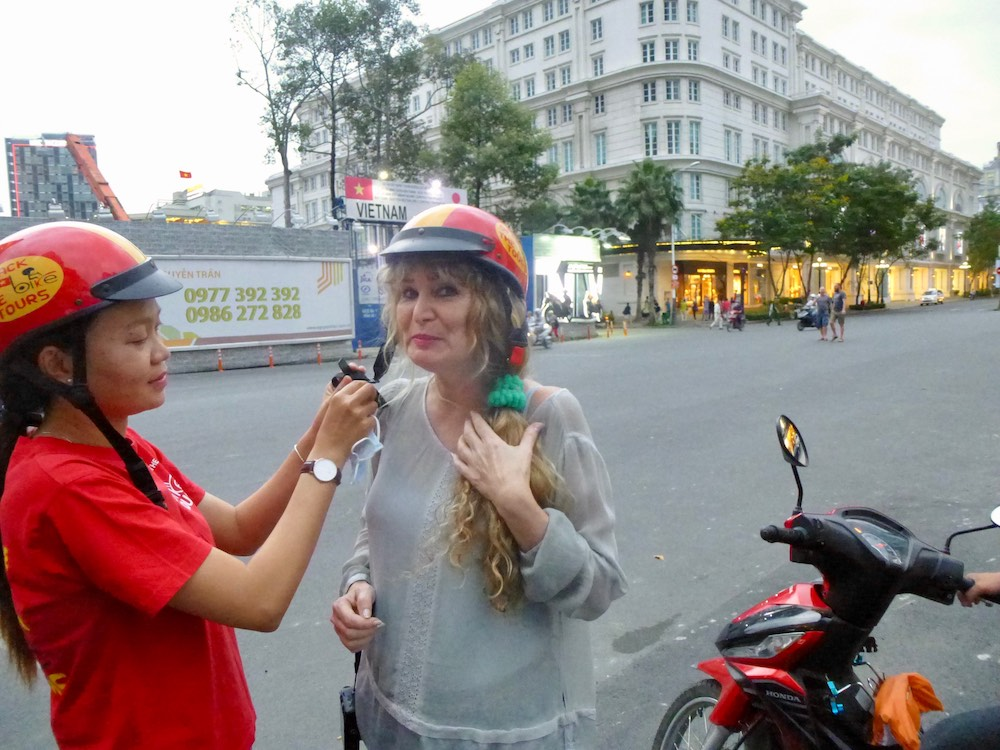 Driver helps passenger close strap of helmet |curlytraveller.com