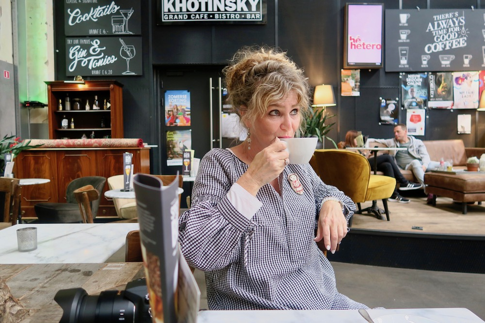 Woman sipping from a cappuccino in Kothinsky Dordrecht |curlytraveller.com