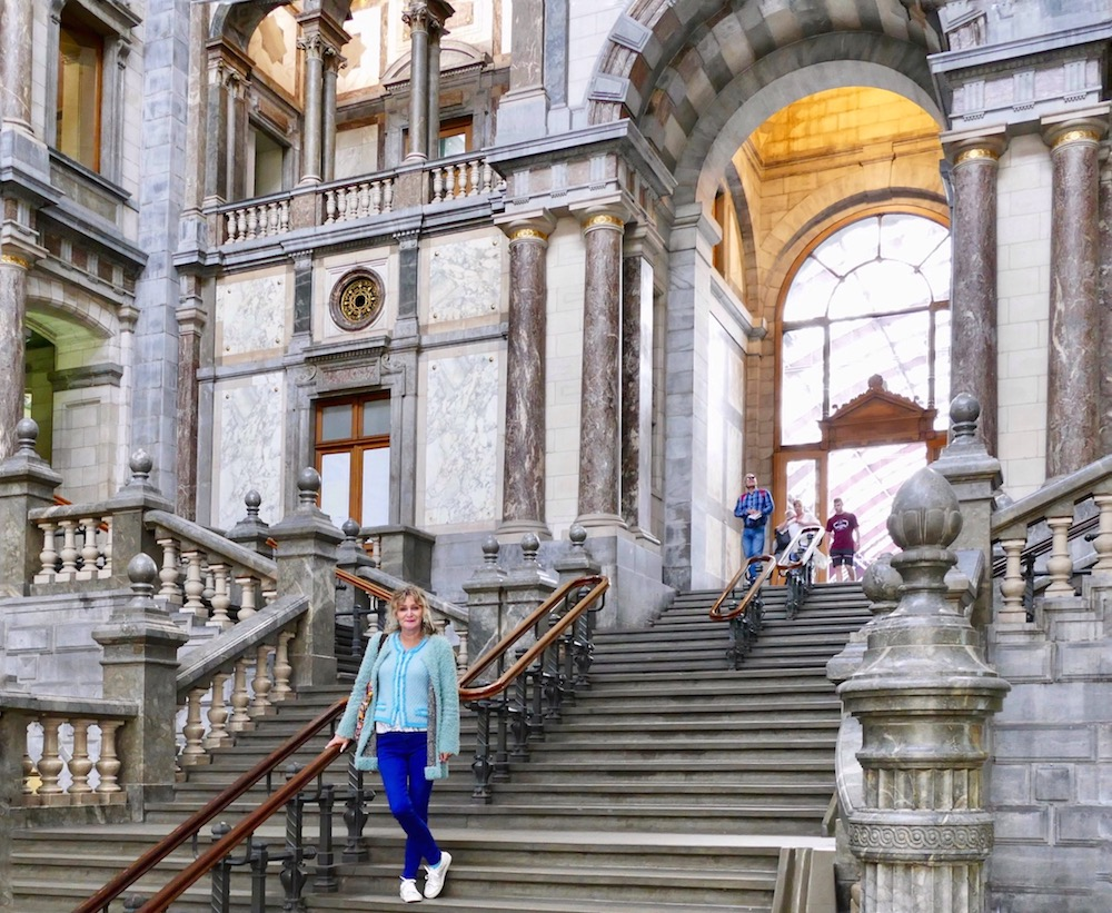 Woman posing on stairs at Antwerpen Centraal |curlytraveller.com