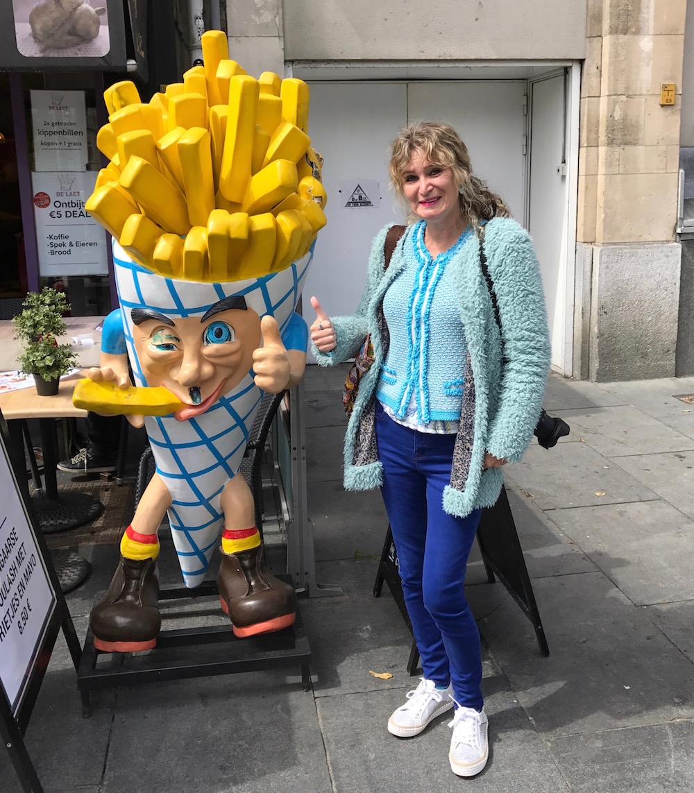 Woman next to advertisement for french fries |curlytraveller.com