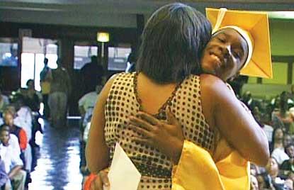 Student hugging principal at graduation