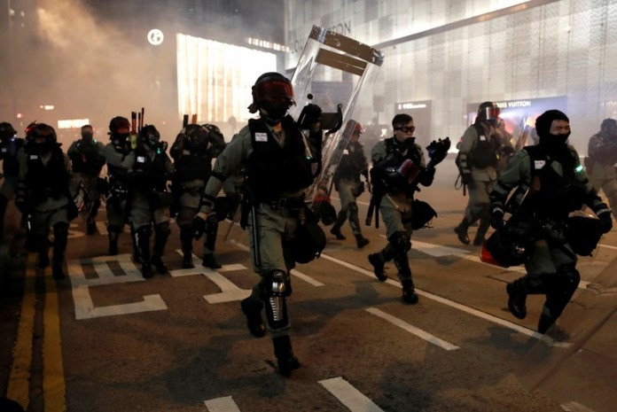Riot police officers walk during a Halloween march in Hong Kong
