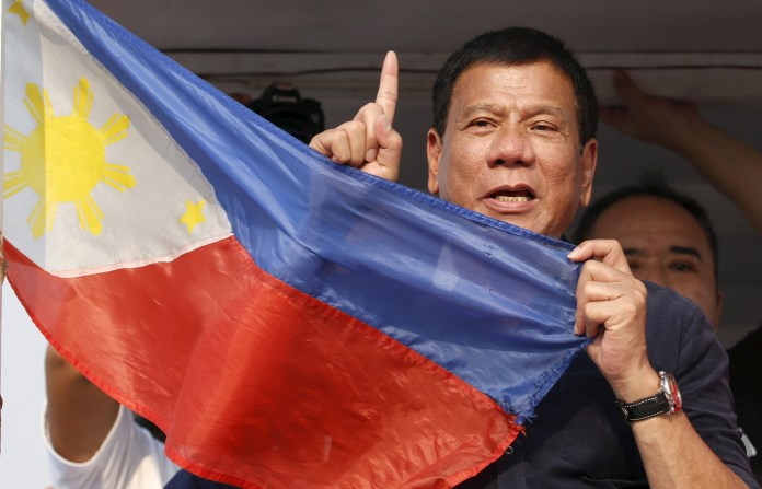 "Presidential candidate Rodrigo ""Digong"" Duterte holds the national flag during election campaigning for May 2016 national elections in Malabon, Metro Manila"