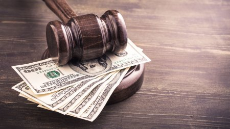 Gavel atop hunded dollar bills feature image