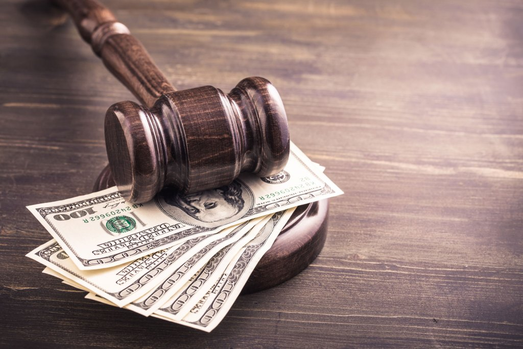 Gavel atop a pile of hundred dollar bills