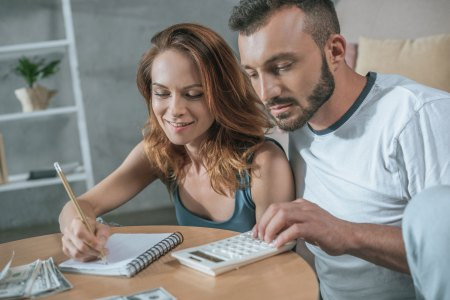 happy couple making a budget with calculator at kitchen table