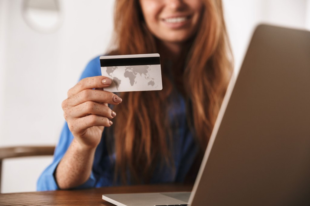 woman holding credit card next to laptop