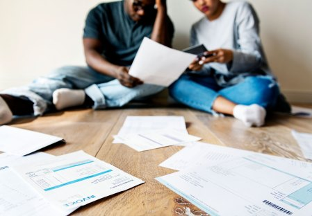 married couple sitting on floor dealing with piles of bills and debt paperwork
