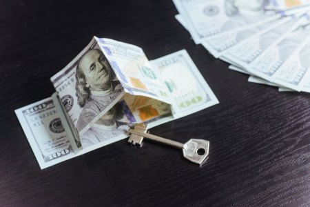 hundred dollar bill in the shape of a house with a key under it surrounded by more bills