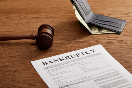 gavel with bankruptcy form in front of a wallet with a hundred dollar bill