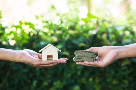hands exchanging a small wooden house for a wad of cash