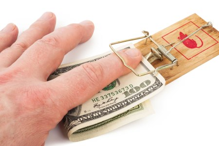 finger getting caught in mouse trap holding money