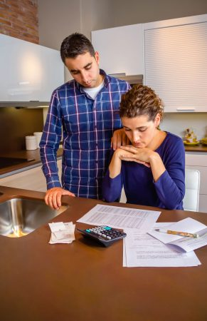 male and female couple looking at unpaid bills on a kitchen table