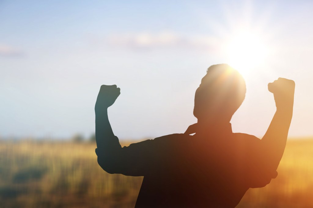 silhouette of man in a field raising his arms in joy