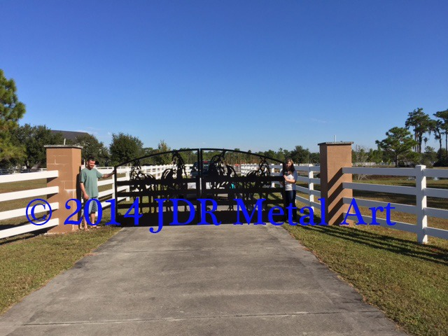 Metal driveway gate featuring custom designed plasma cut horse art silhouettes at Florida horse farm. Made by JDR Metal Art.
