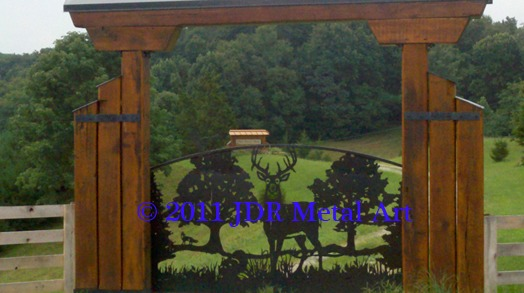 Metal art front driveway gate with silhouettes of deer fox turkey pine oak trees.